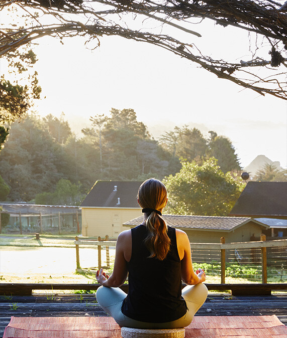 Woman meditating outside of her cottage